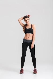 Pełny uśmiechnięty sprawności fizycznej kobiety trening i patrzeć, odizolowywający nad szarości ścianą