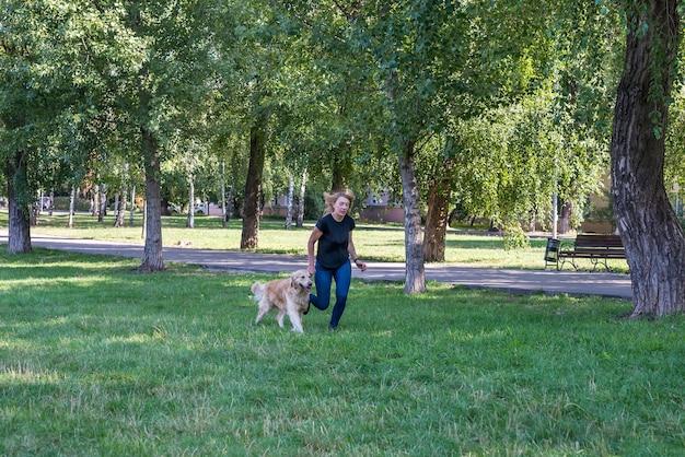 Pełny widok atrakcyjnej dziewczyny spacerującej z psem retriever w parku
