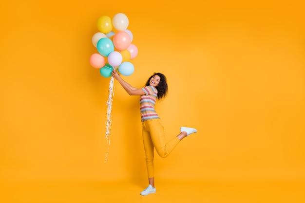 Pełny widok długości dziewczyny trzymającej piłkę powietrzną, ciesząc się uroczysty dzień