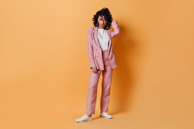 Pełny widok długości kobiety w różowym garniturze