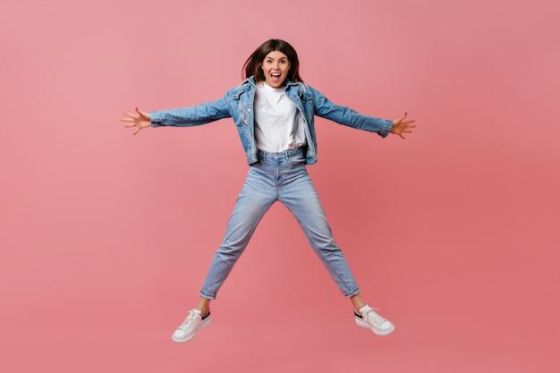 Pełny widok długości niesamowitej dziewczyny w dżinsowym stroju, machającej rękami na różowym tle. młoda kobieta skacze i uśmiecha się.