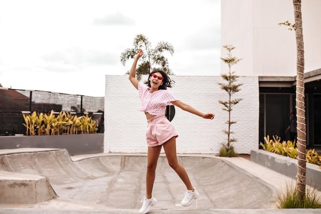 Pełny widok długości opalonej kobiety w krótkich spodenkach skaczących na ulicy. odkryty strzał europejskiej kobiety korzystających z lata.