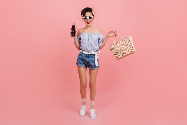 Pełny widok długości pinup girl w okularach przeciwsłonecznych. studio strzałów dobrze ubranej młodej kobiety z sodą i torbą.