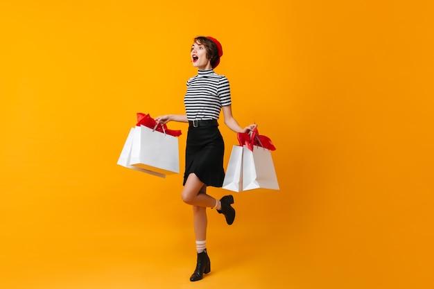 Pełny widok długości podekscytowanej szczupłej kobiety z torbami sklepowymi