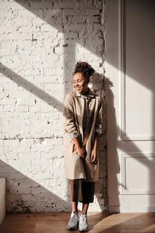 Pełny widok długości roześmianej kobiety w płaszczu