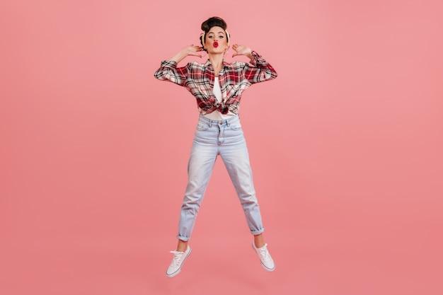 Pełny widok długości skaczącej dziewczyny pinup. strzał studio kobiety w dżinsach i koszuli w kratkę, pozowanie na różowym tle.