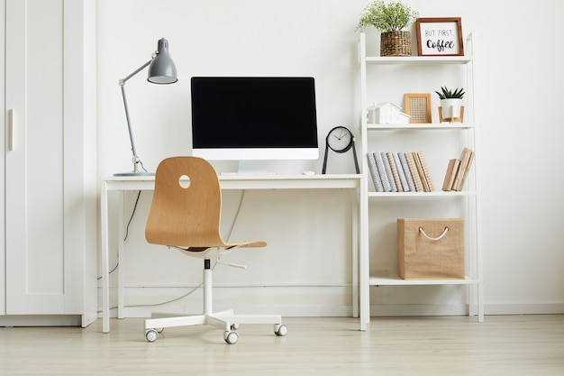 Pełny widok długości w minimalistycznym domowym biurze z drewnianym krzesłem i białym biurkiem na białej ścianie