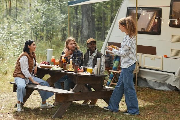Pełny widok na różnorodną grupę przyjaciół korzystających z pikniku na świeżym powietrzu na kempingu z przyczepą kempingową