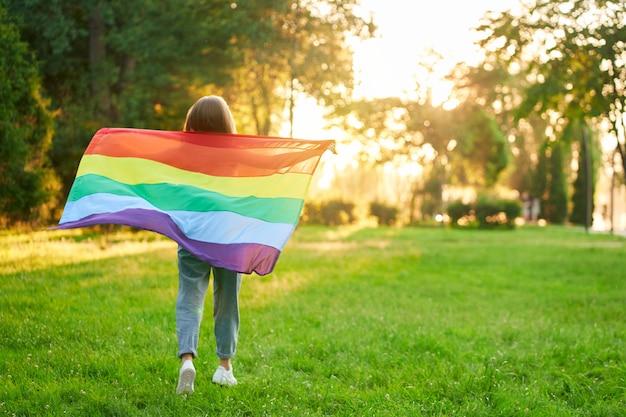 Pełny widok z tyłu nierozpoznawalnej dziewczyny pozującej w parku, cieszącej się letnim zachodem słońca.