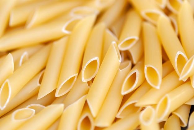 Penne lisce - tradycyjny włoski makaron z pszenicy durum, tło żywności