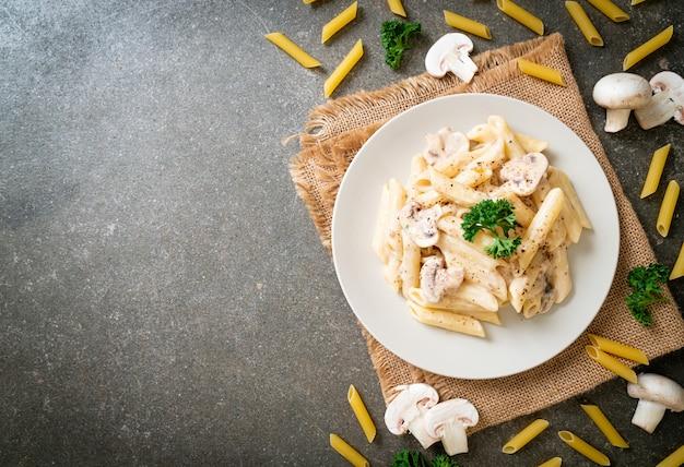 Penne pasta carbonara kremowy sos z grzybami. włoski styl jedzenia