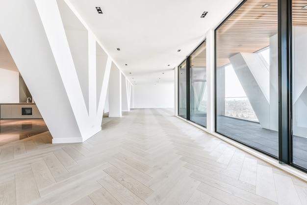 Penthouse wnętrze pokoju typu studio ze szklanymi ścianami i tarasem z widokiem na panoramę miasta w słońcu
