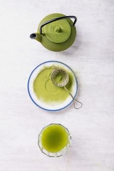 Peparacja herbaty matcha: różne przybory do herbaty matcha na szarym drewnie, widok z góry