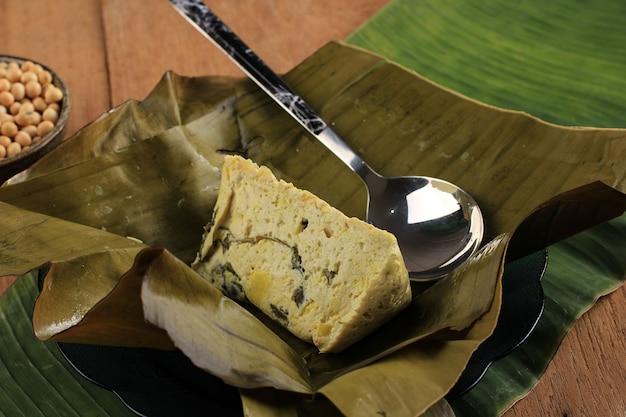Pepes tahu to indonezyjskie tofu w przyprawach, owijane liściem bananowca i gotowane na parze, typowo indonezyjskie jedzenie z zachodniej jawy (sundanese). tofu gotowane na parze z bazylią azjatycką, zbliżenie