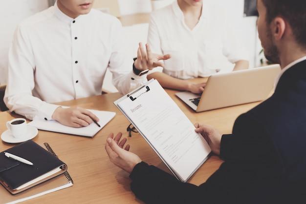 Pepole omawiający cv na rozmowie kwalifikacyjnej w biurze