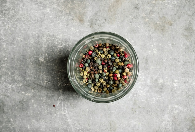 Peppercorn w szklanym spodku na kamieniu.