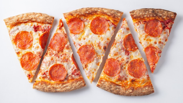 Pepperoni pizzy plasterki na białym tle. top.
