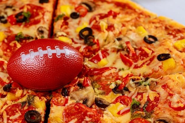 Pepperoni supreme pizza z piłką futbolową na imprezę futbolu amerykańskiego.