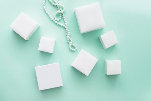 Perełkowa kolia z różnymi białymi pudełkami na turkusowym tle
