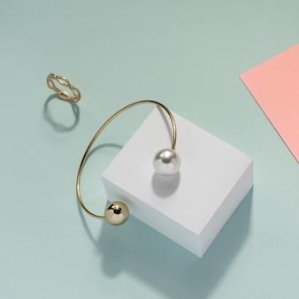 Perełkowa złota bransoletka i złoty pierścionek na błękitnym tle