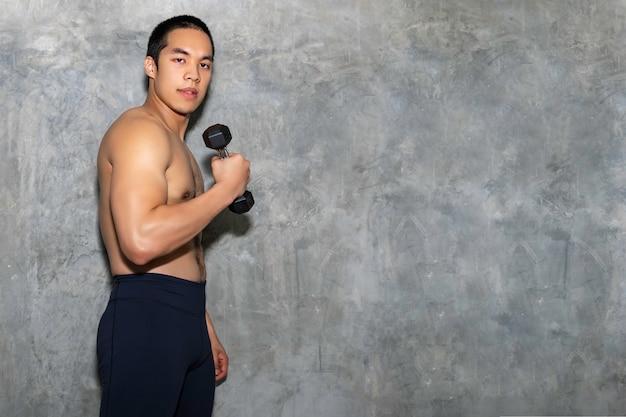 Perfect silnego kulturysty sportowa azjatycka mężczyzna treningu ręka z hantle na tle.