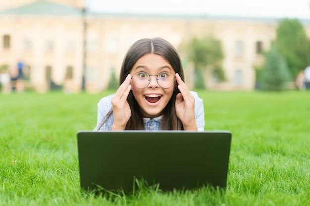 Perfekcyjny dzień. rozpocząć. dziecko grając w grę komputerową. powrót do szkoły. edukacja online. dzień wiedzy. dziecko uczy się prywatnej lekcji. blogowanie. szczęśliwa dziewczyna siedzi na zielonej trawie z laptopem.