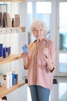 Perfumeria. siwowłosa kobieta wybierająca perfumy w butiku