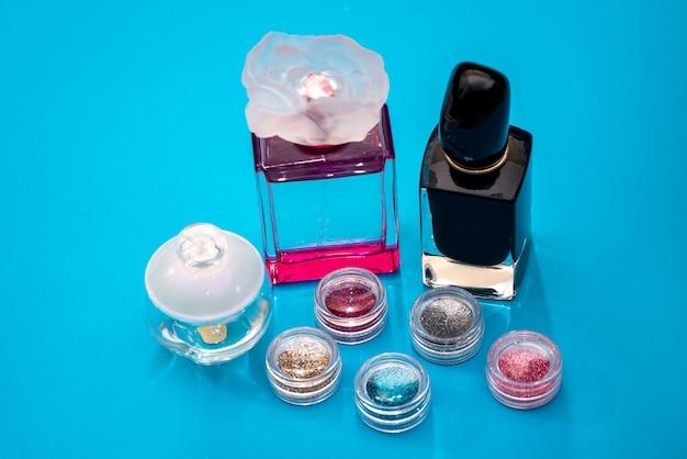 Perfumy damskie i błyszczy paznokci na niebieskim tle
