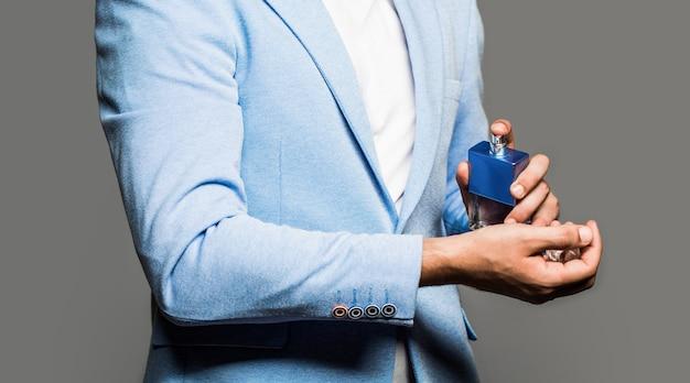 Perfumy dla mężczyzn perfumy męskie mężczyzna trzyma butelkę perfum