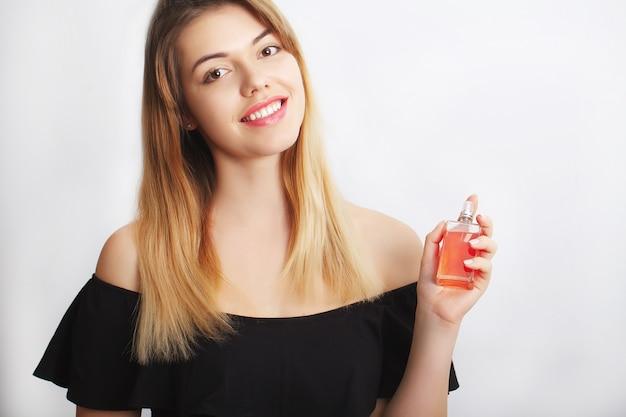 Perfumy. młoda ładna kobieta z przyjemnością pachnący aromatem