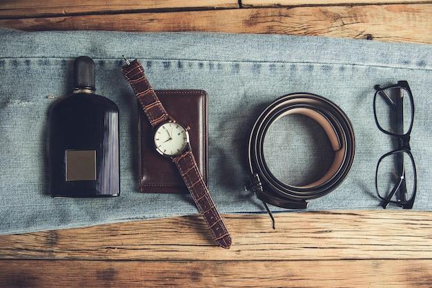 Perfumy z portfelem i paskiem z okularami na dżinsach