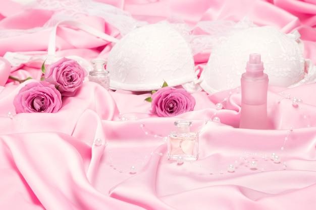Perfumy z różami i kobiecą bielizną na różowym jedwabiu. wybór zapachu do koncepcji romantycznej randki