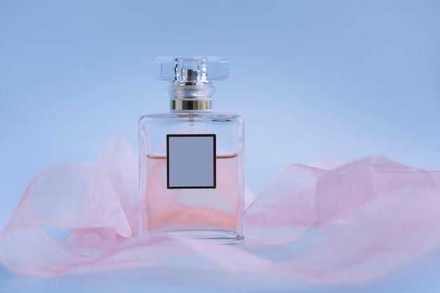 Perfumy z różowymi wstążkami na niebieskim tle