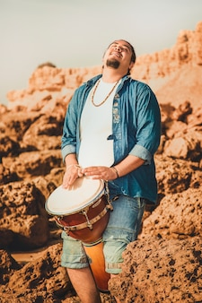 Perkusista boho grający w bębnie na plaży na kamieniach