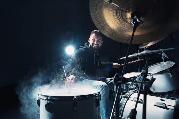 Perkusista ćwiczy na perkusji przed koncertem rockowym. mężczyzna nagrywający muzykę na zestawie perkusyjnym w studio z efektem pokazowym w postaci mąki