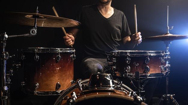 Perkusista gra na perkusji siedząc przy zestawie perkusyjnym na scenie