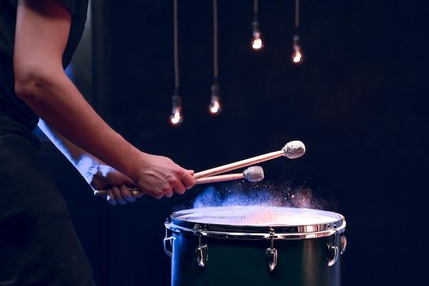 Perkusista gra patykami na podłodze w ciemnym pomieszczeniu z pięknym oświetleniem. koncepcja koncertu i performansu.