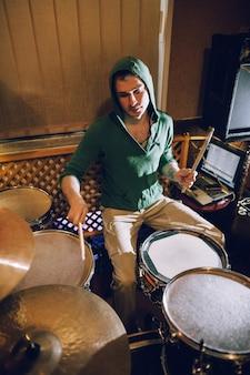 Perkusista grający na zestawie perkusyjnym w studiu nagraniowym