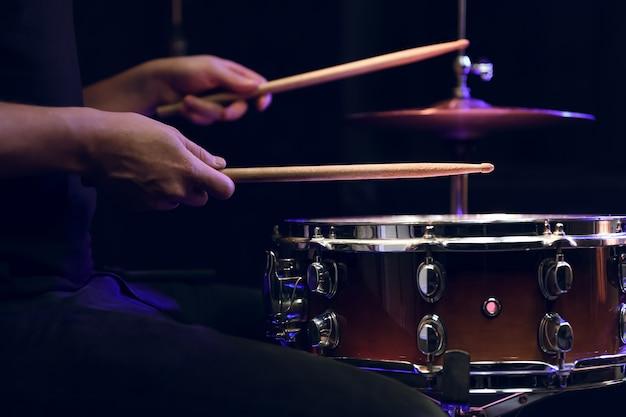 Perkusista grający pałkami perkusji na werblu w ciemności. koncepcja koncertu i występów na żywo.