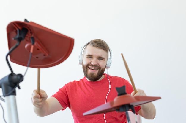 Perkusista, hobby i koncepcja muzyki - młody perkusista mężczyzna w czerwonej koszuli gra na perkusji elektronicznej.