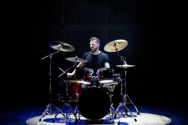Perkusista sylwetka na scenie. ciemne tło, reflektory dymne.