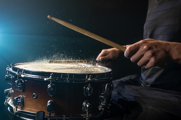 Perkusista za pomocą pałeczek perkusyjnych uderzając werbel z rozpryskiwaniem wody na czarnym tle pod oświetleniem studyjnym z bliska.