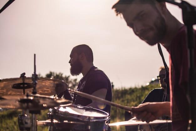 Perkusista zespołu rockowego gra na swoich bębnach na pierwszym planie, za basistą robi swoje