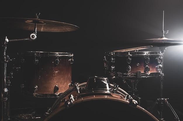 Perkusja, bęben basowy, hi-hat, talerze na ciemnym tle z wiązkami z reflektora, kopia przestrzeń.