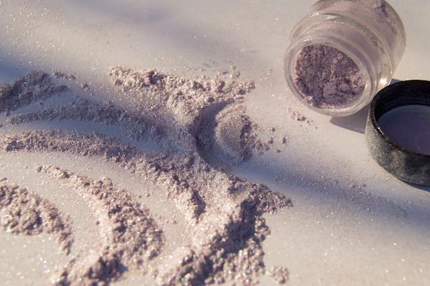 Perłowy cienie do powiek rozrzucony na stole, słoik cieni
