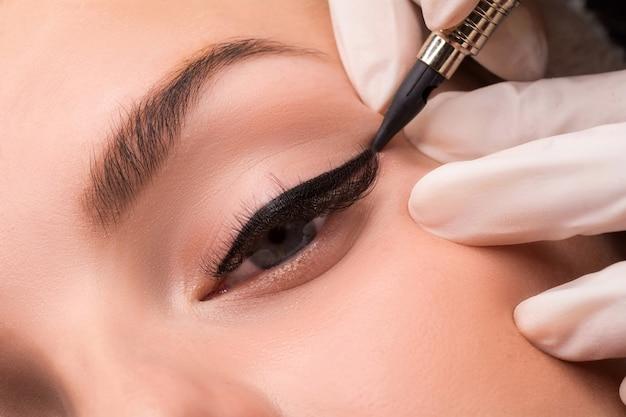 Permanentny makijaż oczu z bliska strzał. kosmetolog wykonujący tatuowanie oczu. procedura makijażu eyeliner.