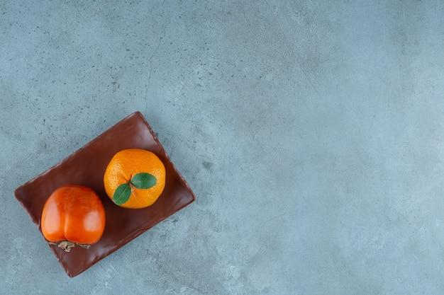 Persimmon i pomarańcza na drewnianym talerzu, na marmurowym stole.