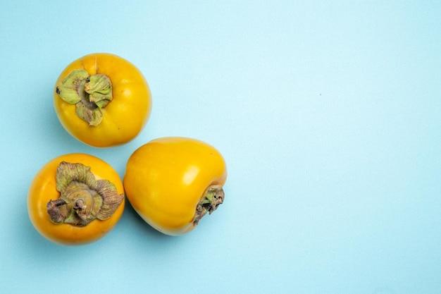 Persimmons trzy apetyczne persimmons po lewej stronie stołu