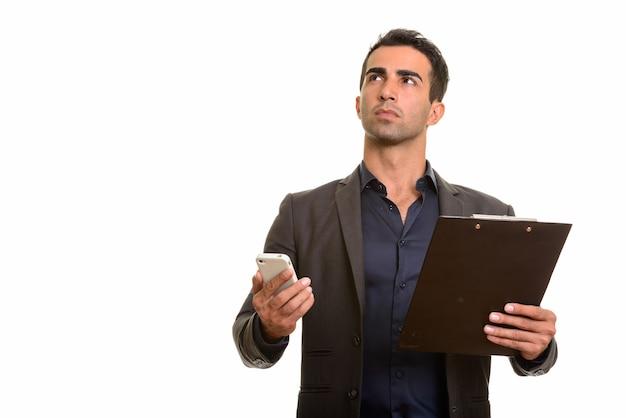 Perski biznesmen przy użyciu telefonu i trzymając schowek