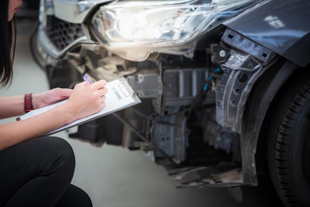 Personel agenta ubezpieczeniowego zapisuje w schowku podczas sprawdzania samochodu po ocenie i przystąpił do dochodzenia roszczenia z tytułu wypadku - samochód ma ubezpieczenie wypadkowe.